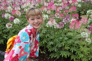 花の前に立っている女の子の写真・画像素材[1289494]