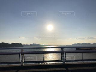 水体を見下ろすベンチに座る人の写真・画像素材[988054]