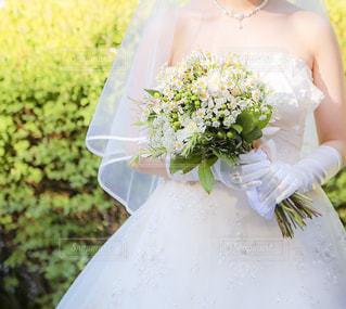 白いウェディング ドレスとテーブルの上の花の花瓶の写真・画像素材[1249127]