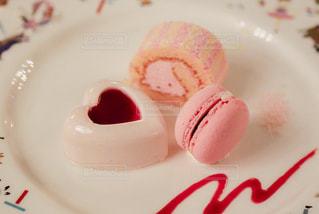 近くに皿の上のピンクと白のケーキのアップの写真・画像素材[1249512]