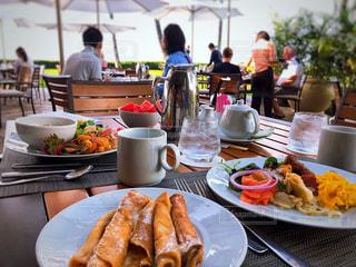 食品のプレートをテーブルに座っている人々 のグループの写真・画像素材[1168887]