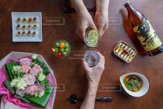 テーブルに食べ物のプレートを持っている人の写真・画像素材[1444686]