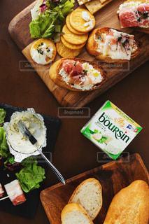 木製のテーブルの上に座っている食べ物の束の写真・画像素材[3235470]