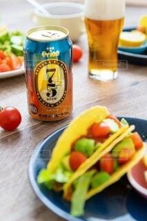 食べ物の皿と一杯のビールをテーブルの上に置いての写真・画像素材[3929329]