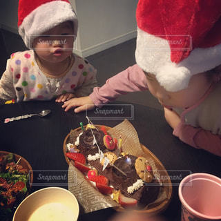 子ども,冬,ケーキ,女の子,ろうそく,人物,人,クリスマス,食べる,こども,姉妹,クリスマスケーキ,サンタ帽子,ふーっ