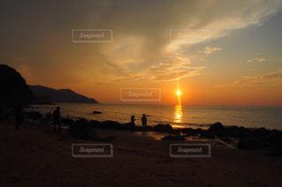 ビーチでの背景の夕日に人々 のグループの写真・画像素材[851303]
