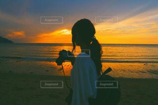 水の体の上に日没の前に立っている人の写真・画像素材[1295984]