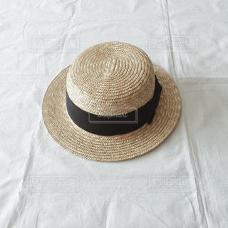 テーブルの上に座って帽子が付いているベッドの写真・画像素材[1221500]