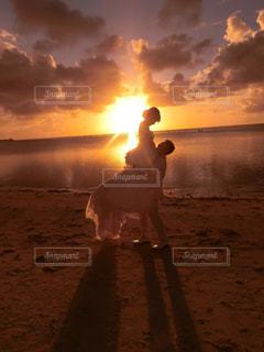 日没の前にビーチに立っている人の写真・画像素材[971037]