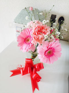 ピンクの花の花束 赤いリボンの写真・画像素材[997863]