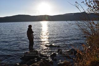 水の体の横に立っている人の写真・画像素材[967829]