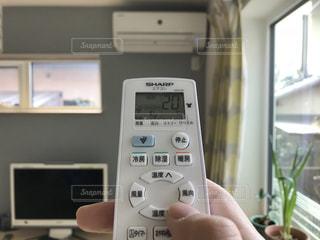 エアコンのリモコンを操作する手の写真・画像素材[969454]