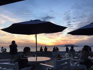 曇りの日にビーチ パラソルに座っている人々 のグループの写真・画像素材[969604]