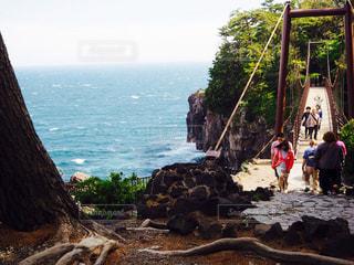 水の体の横にある岩の上の人々 のグループの写真・画像素材[1034040]