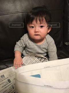 新聞を読んで時事ネタを勉強するゆうきボーイの写真・画像素材[988416]