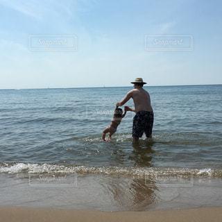 海の横にあるビーチの上を歩く男の写真・画像素材[972407]
