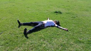 緑豊かな緑のフィールドに寝てる人の写真・画像素材[985191]