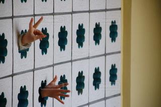 壁から出るちびっこの手の写真・画像素材[1871740]