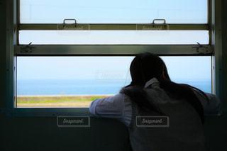 電車の窓を開けて外を見ているJKの写真・画像素材[1017384]