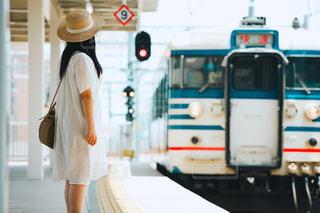 ホームで電車を待つ白のワンピースを着た女の子の写真・画像素材[2271940]