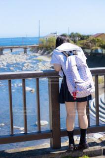 橋の上から川を眺める女子高生の写真・画像素材[3325985]