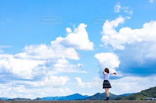 防波堤の上で手を広げて、風を感じている女子高生の写真・画像素材[3325987]