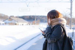 雪晴れの駅のホームで電車を待つ女子高生の写真・画像素材[3328121]