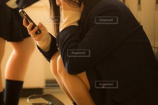スマホを見ながらしゃがみこみ、何か考えごとをしている女子高生の写真・画像素材[3328119]