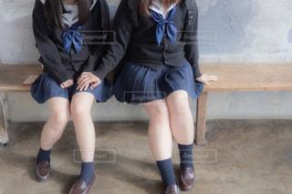 ベンチに座って相手の子の手に自分の手を乗せ想いを伝える女子高生の写真・画像素材[3328131]