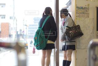 雨で肌寒い中、駅で待っている女子高生2人の写真・画像素材[3328177]