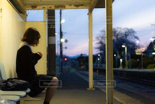 駅ホームのベンチで寒さに震えるカーディガン姿の女子高生の写真・画像素材[3328180]