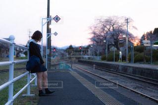 ホームで電車を待つカーディガン姿の女子高生の写真・画像素材[3328185]