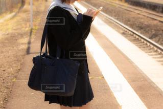 ホームで電車を待つカーディガン姿の女子高生(セーラー服)の写真・画像素材[3328186]