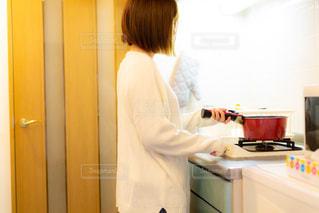 キッチンで料理を作っているカーディガン姿の若い女性の写真・画像素材[3328178]