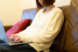 ソファに座りノートパソコンで作業をしている若い女性の写真・画像素材[3328195]