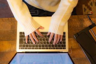 木製のテーブルの上でノートパソコンで作業する若い女性の写真・画像素材[3328184]