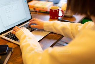 テーブルでノートパソコンでの作業をするカーディガン姿の若い女性の写真・画像素材[3328183]