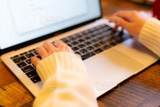 ノートパソコンで作業をするカーディガン姿の女性の写真・画像素材[3328187]