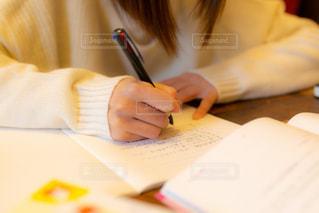 勉強か仕事でノートに字を書くカーディガン姿の女性の写真・画像素材[3328193]