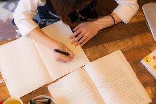 自宅にある木のテーブルで勉強する女子高生の写真・画像素材[3349934]