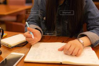 ノートに何か書いている女性の手元の写真・画像素材[3349942]