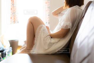 寝起きでぼーっとしてソファに座る女性の写真・画像素材[3367942]
