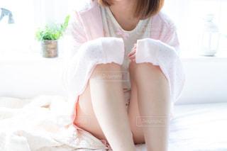 ベッドの上にひざをかかえて座っている女性の写真・画像素材[3367944]