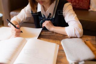 自宅のリビングで制服姿で勉強する女子高生の写真・画像素材[3433201]
