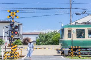 踏切で江ノ電の通過待ちをする若い女性の写真・画像素材[3496279]