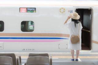 新幹線の前に立つ若い女性の写真・画像素材[3496277]