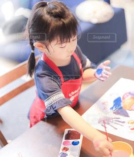 テーブルの上に座っている小さな子供の写真・画像素材[3171306]