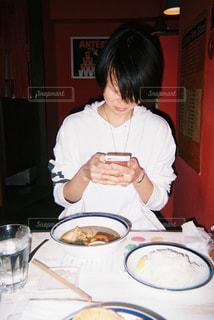 食品のプレートをテーブルに着席した人の写真・画像素材[1029831]