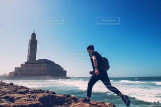 岩のビーチに立っている人の写真・画像素材[1001467]
