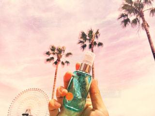 レールデュサボンのボトルを持っている手と空の写真・画像素材[1181348]
